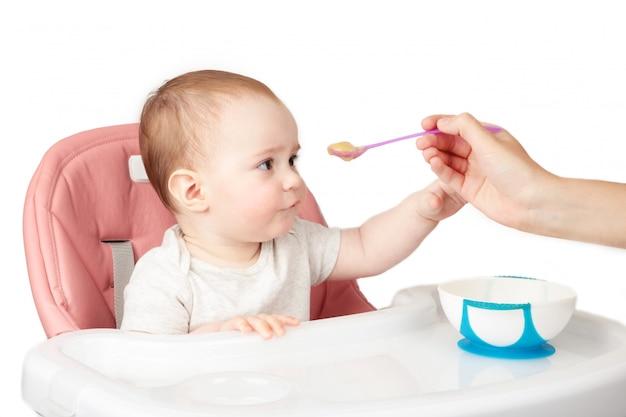 Mutter füttert ihr niedliches baby im stuhl auf grauem hintergrund.