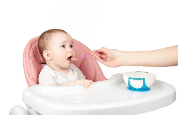 Mutter füttert ihr niedliches baby im stuhl lokalisiert auf weißem hintergrund.