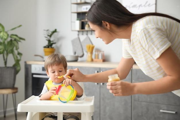 Mutter füttert ihren kleinen sohn in der küche