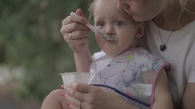 Mutter füttert kleine tochter draußen