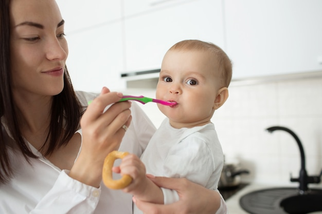 Mutter füttert süßes baby mit löffel