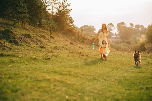 Mutter geht mit seiner kleinen tochter und ihrem hund spazieren