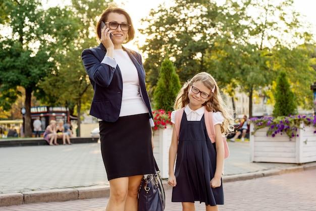 Mutter geschäftsfrau bringt das kind zur schule.