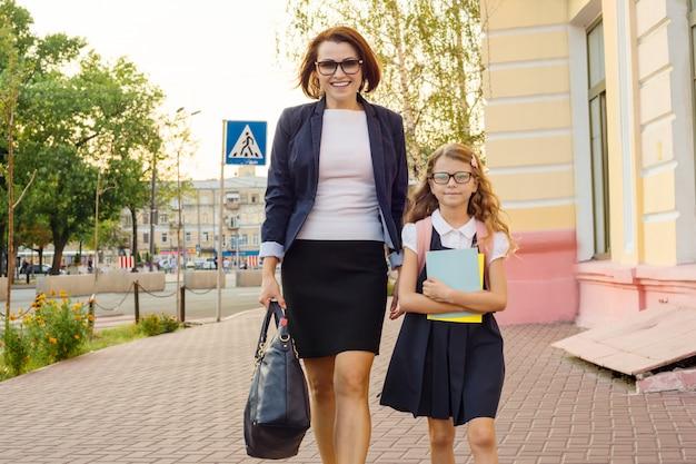 Mutter geschäftsfrau bringt das kind zur schule