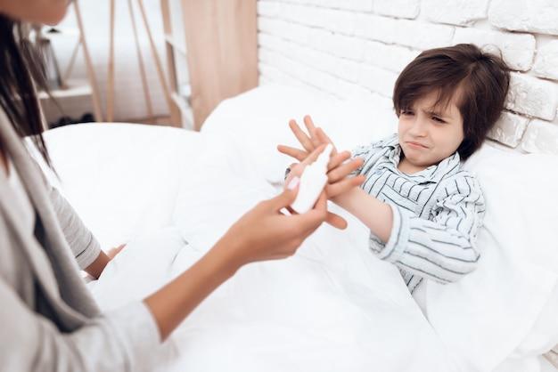 Mutter gibt einem kranken sohn zu hause medizin.