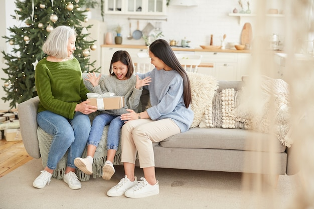 Mutter gibt geschenk für ihre jüngere tochter am weihnachtstag, während sie auf sofa im wohnzimmer sitzen