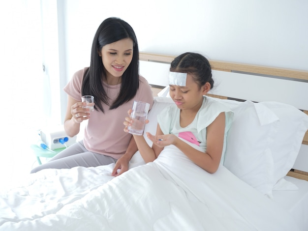 Mutter gibt ihrer tochter medizin, aber ihre tochter mag es nicht.