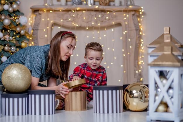 Mutter gibt seinem kleinen sohn ein weihnachtsgeschenk für ein neues jahr. mutter und sohn öffnen weihnachtsgeschenke