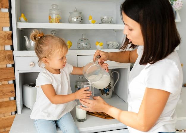 Mutter gießt milch für ihre schöne tochter