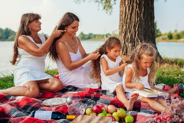 Mutter, großmutter und kinder, die zöpfe miteinander spinnen. familie, die spaß während des picknicks im park hat. drei denerationen