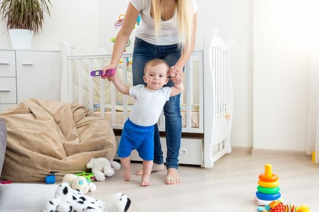 Mutter hält baby an den händen und geht im wohnzimmer