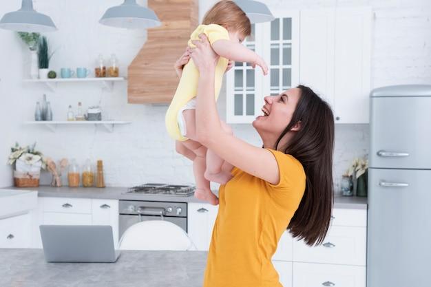 Mutter hält baby in der küche