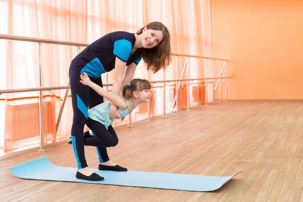 Mutter hält eine tochter in ihren armen, die eine übungsgymnastik durchführt.