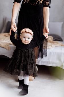 Mutter hält hände tochter genießen zeit zusammen zu hause. blick auf die beine. muttertag, babytag. konzept des jungen familienurlaubs und pflege der liebe und unterstützung für die nächste generation.