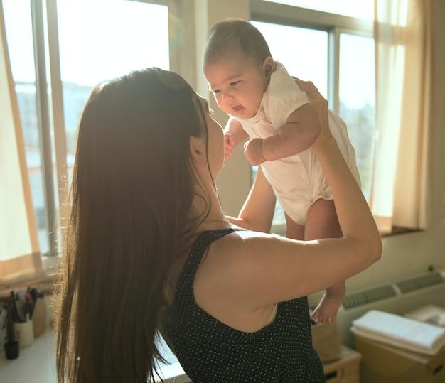 Mutter hält ihr baby in liebe hoch