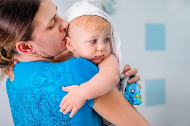 Mutter hält ihr baby nach dem baden in den armen.