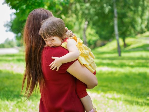 Mutter hält ihr weinendes einjähriges baby mit tränen in der nähe