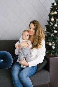 Mutter hält ihren kleinen sohn in den armen und sitzt auf der couch neben dem weihnachtsbaum. neujahr feierlichkeiten