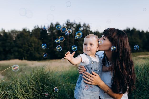 Mutter hält kleine tochter auf ihren armen, während seifenballons um sie herum fliegen