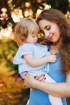 Mutter hält sanft kleine tochter in ihren armen.