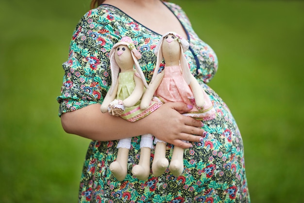 Mutter hände halten zwei kaninchen. bauch der schwangeren frau. zwillinge