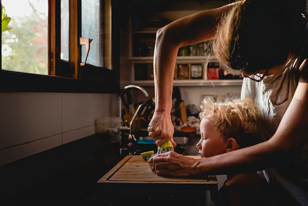 Mutter half ihrem sohn, obst zu pressen.