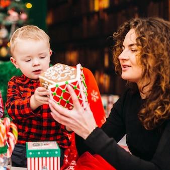 Mutter hat spaß mit ihrem sohn, der im raum sitzt, der für weihnachten und neues jahr gekleidet wird