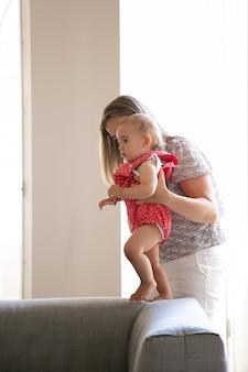 Mutter hilft baby, zu hause zu gehen. kind macht erste schritte mit mutter unterstützung. seitenansicht. elternschafts- und kindheitskonzept