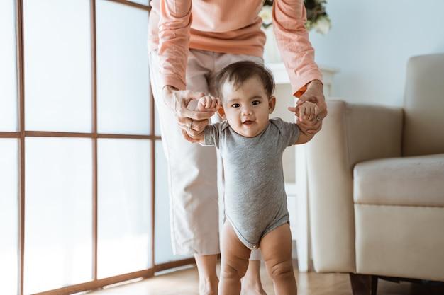Mutter hilft ihrem baby, ihre ersten schritte zu hause zu gehen