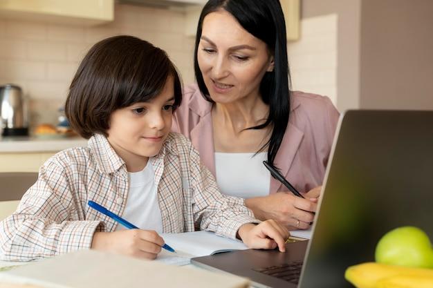 Mutter hilft ihrem sohn in einem online-kurs