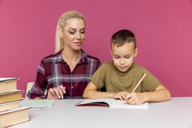 Mutter hilft ihrem sohn, zu hause zu lernen. schule wegen quarantäne geschlossen.