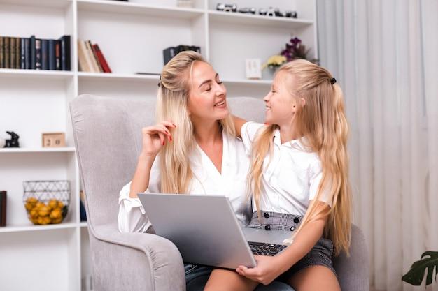 Mutter hilft ihrer kleinen tochter, wie man einen computer benutzt