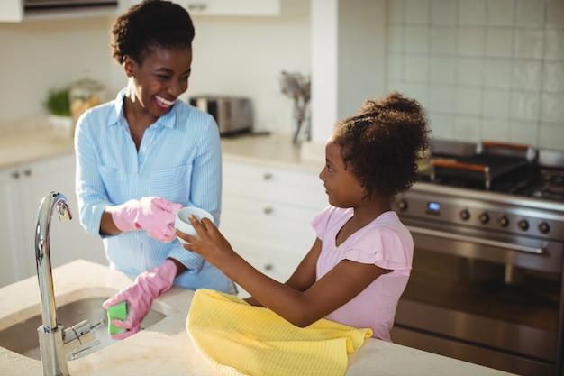 Mutter hilft ihrer tochter beim putzen von utensilien