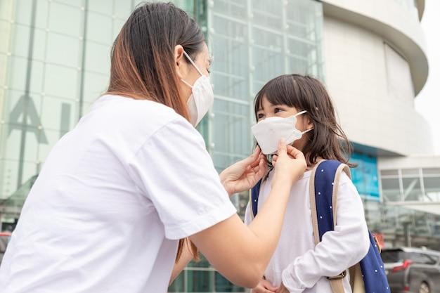 Mutter hilft ihrer tochter beim tragen einer medizinischen maske zum schutz des ausbruchs von covid19