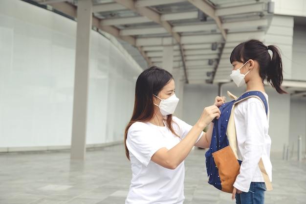 Mutter hilft ihrer tochter, die eine medizinische maske zum schutz von covid19 trägt, sich auf den schulbesuch vorzubereiten