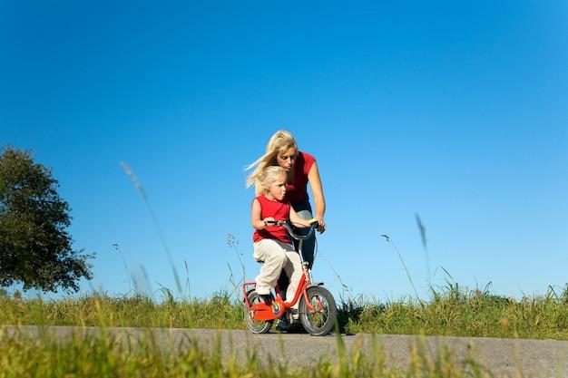 Mutter hilft ihrer tochter fahrrad zu fahren