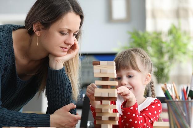 Mutter hilft ihrer tochter geduldig beim aufbau der struktur