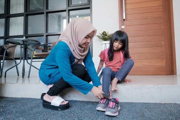 Mutter hilft ihrer tochter, morgens schuhe zu tragen, während sie sich auf den schulbesuch vorbereitet