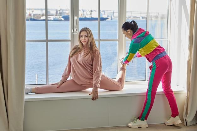 Mutter hilft ihrer tochter zu hause beim stretching, um auf bindfäden sitzen zu können