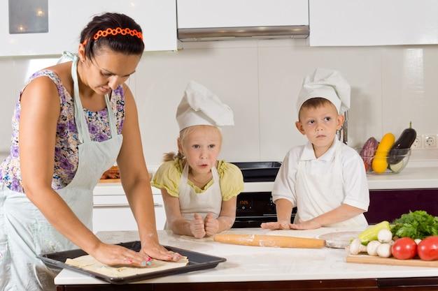 Mutter hilft koch-kindern bei der zubereitung von speisen in der küche