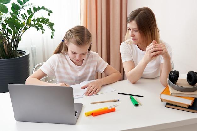 Mutter hilft tochter, hausaufgaben zu machen. das konzept der häuslichen erziehung in quarantäne. schwierigkeiten beim fernunterricht