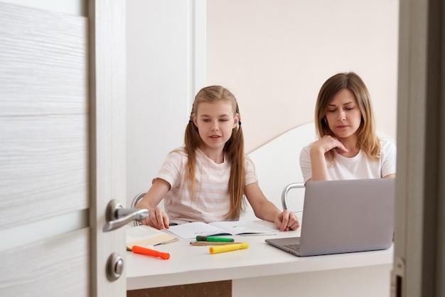 Mutter hilft tochter, hausaufgaben zu machen. konzept der häuslichen bildung in quarantäne. spaß beim fernunterricht