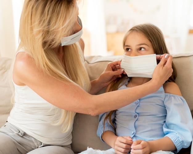 Mutter hilft tochter, medizinische maske aufzusetzen