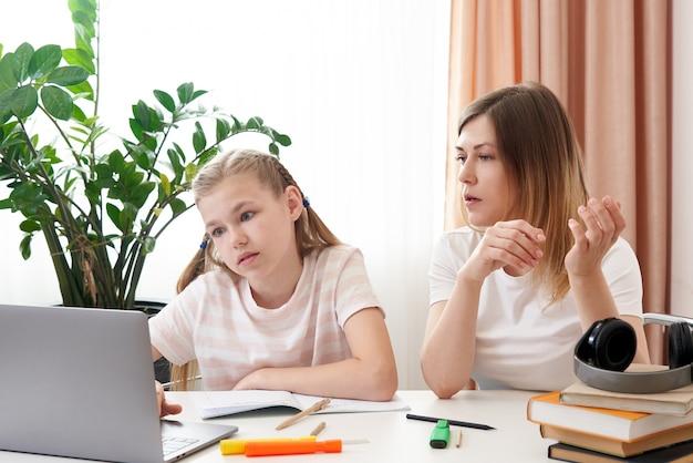 Mutter hilft trauriger tochter, hausaufgaben zu machen. das konzept der häuslichen erziehung in quarantäne. schwierigkeiten beim fernunterricht