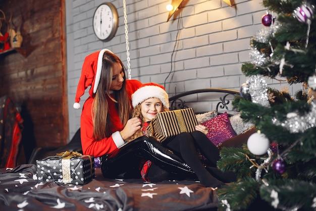 Mutter im weihnachtsmannanzug mit süßer tochter zu hause