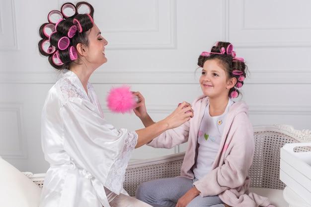 Mutter in den lockenwicklern, die parfüm auf töchternhals anwenden