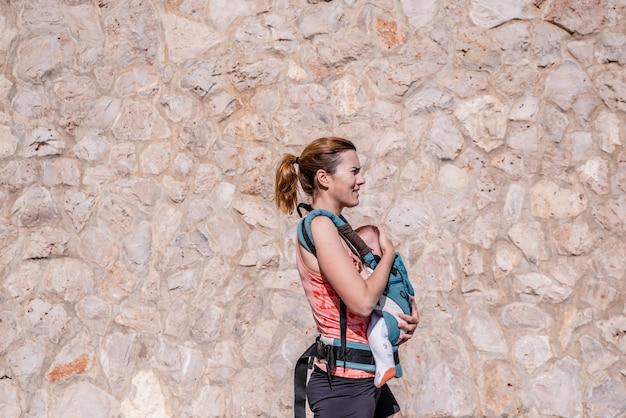 Mutter in der sportkleidung gehend ihr baby in ihrer babytrage.