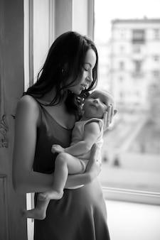 Mutter in einem nachthemd hält einen neugeborenen jungen am fenster in den armen
