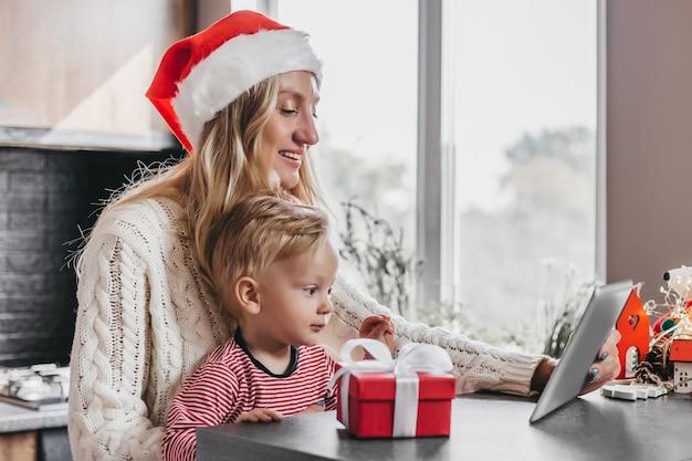 Mutter in santas hut und kleiner sohn sitzen am tisch, halten eine tablette in den händen und unterhalten sich per videokonferenz