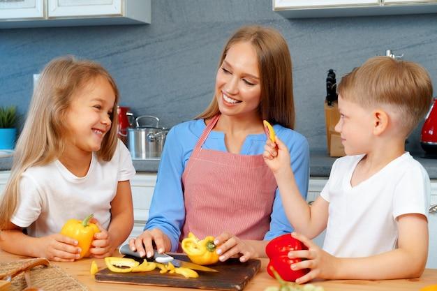 Mutter kocht mit ihren kindern in der küche
